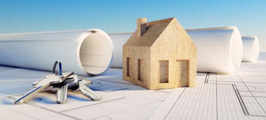 Modellhaus aus Holz auf Bauplänen mit Hausschlüssel - bildlich Immobilienrecht