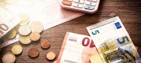 Geld auf Tisch mit Taschenrechner - bildlich für Kosten im Erbrecht