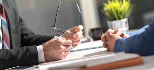 Hände verhandeln am Schreibtisch - bildlich für Testamentsvollstrecker