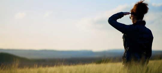 Frau schaut über abendrote Felder zum Horizont - bildlich für Vorsorge