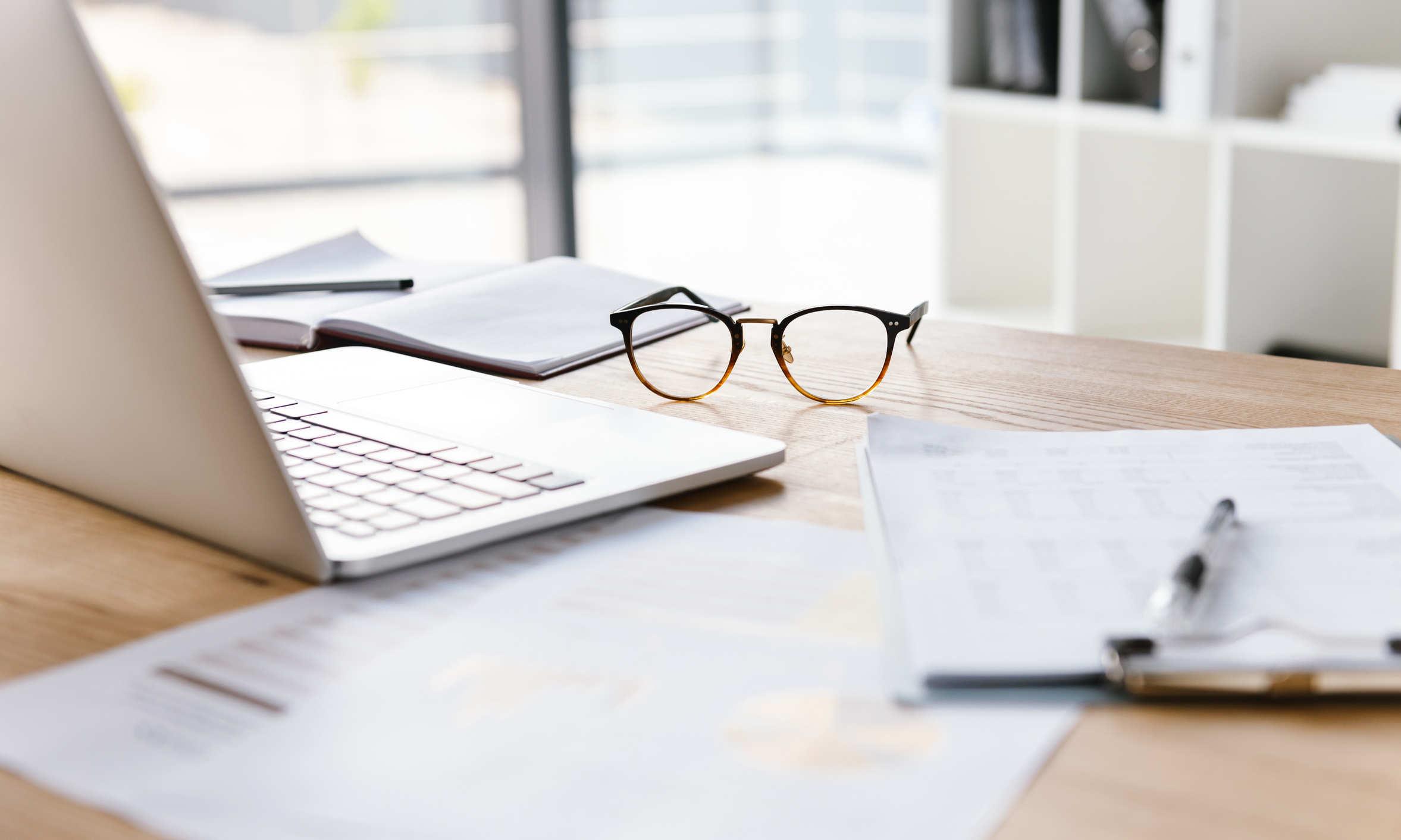 Arbeitsplatz mit Brille, Laptop und Unterlagen - bildlich Arbeitsrecht