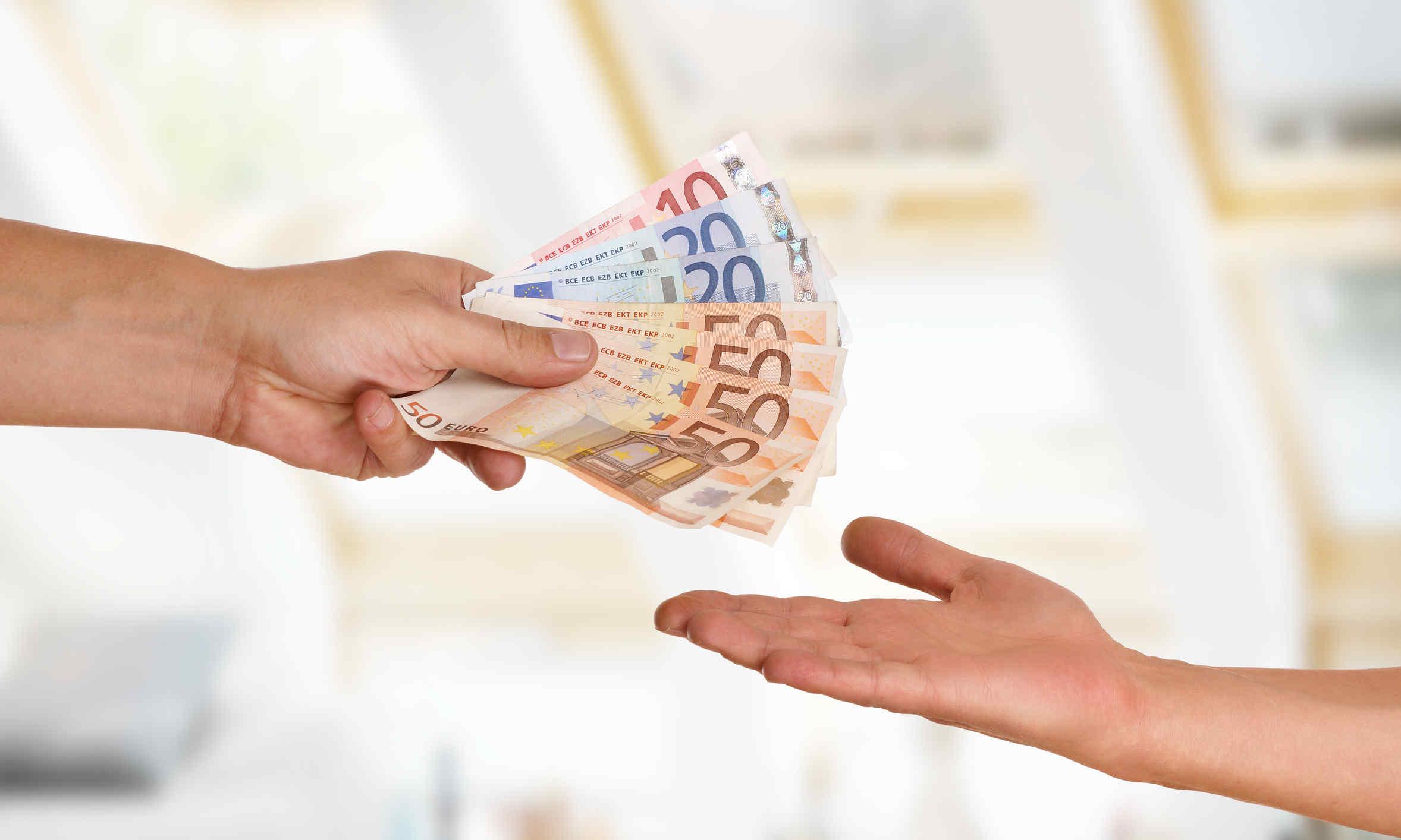 Zwei Hände tauschen Geld aus - symbolisch für die Abgabe des Pflichtteils im Erbrecht