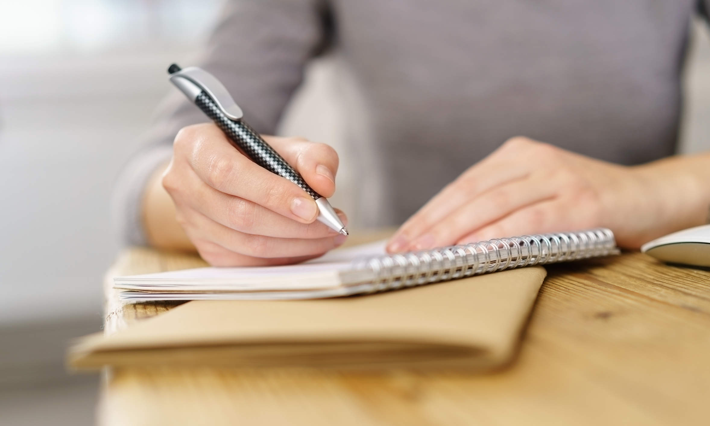 Hände mit Tisch und Notizblock beginnen ein handschriftliches Testament