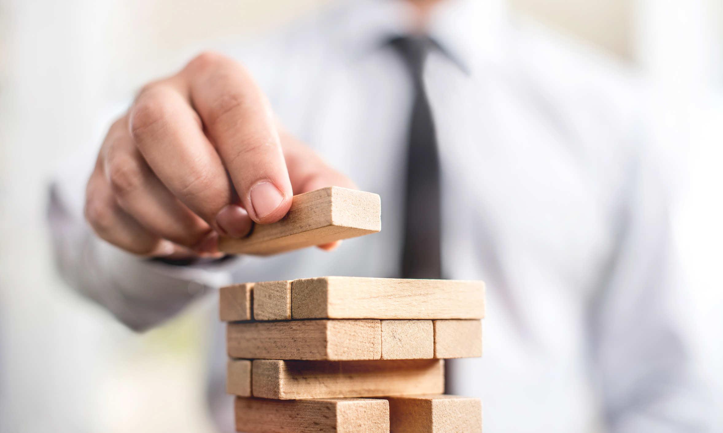 Geschäftsmann stapelt Holzbausteine zu einem Turm - bildlich für strategische Überlegungen bei Schenkungen und Erbschaftssteuer