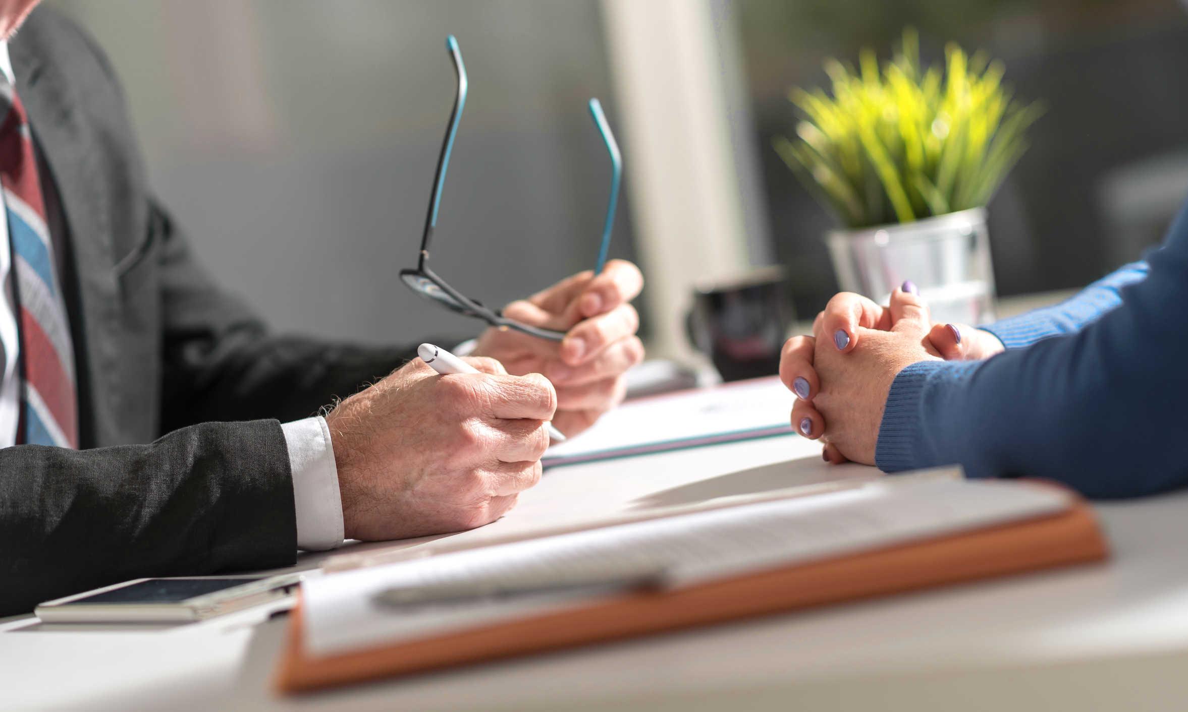 Hände von zwei verhandelnden Personen am Schreibtisch - bildlich für Testamentsvollstrecker